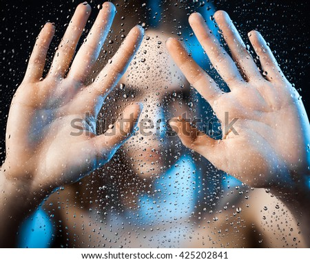 Lonely women with outstretched hand. In the glass. - stock photo