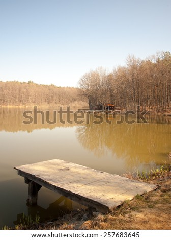 lonely wooden dock on a sunny day in autumn with calm water - stock photo