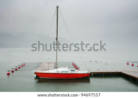 Lonely yacht on stormy weather - stock photo