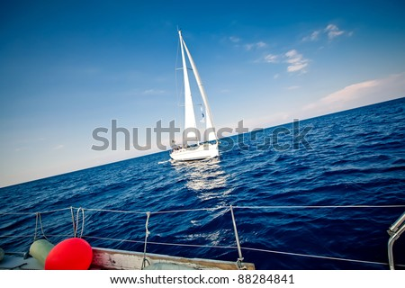 Lonely yacht with white sail in open sea