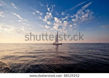 Lonely yacht with white sail in open sea at sunset