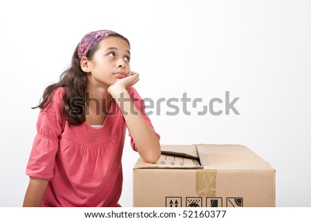 Lonely young girl feeling sad, resting on a cardboard box. - stock photo