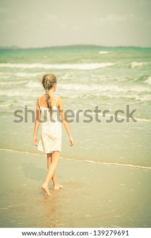 Lonely young girl walking on the beach - stock photo
