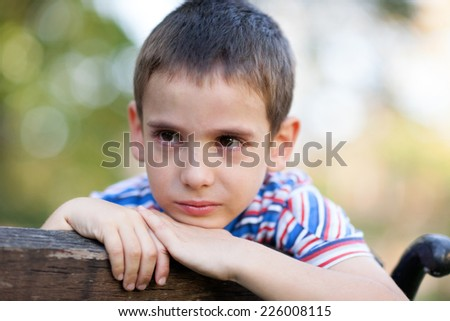 lonely young orphan in park crying - stock photo