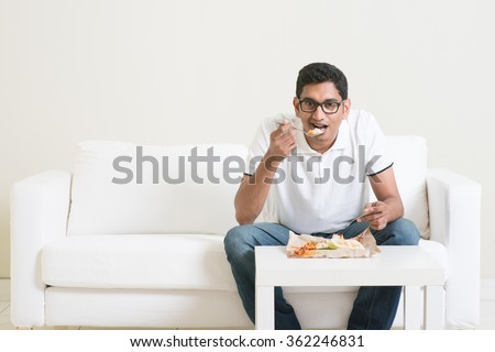 Lonely young single Indian man eating food alone, copy space at side. Having nasi lemak as lunch. Lifestyle of Asian guy at home. - stock photo