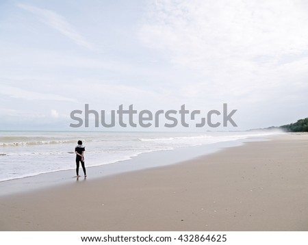 Lonely young woman in black suit walking alone on the beach with high wave as storm in front of her. Abstract - brave woman fighting with hard thing in her live.