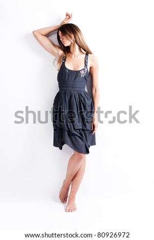 lonely young woman in blue dress, stand, studio shot, full body shot - stock photo