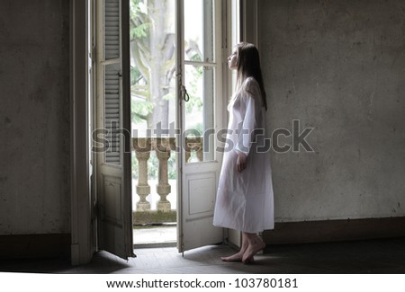 Lonely young woman looking out of a window - stock photo