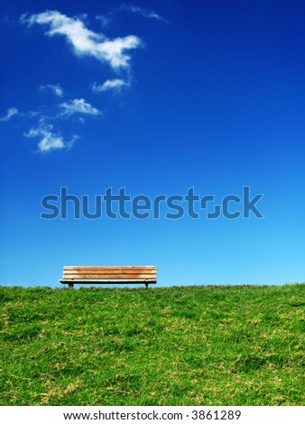 lonesome bench on green grass under a deep blue sky with some white clouds - stock photo