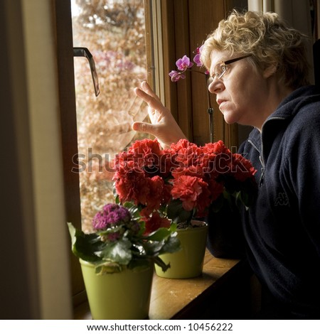 lonesome elderly woman looking outside