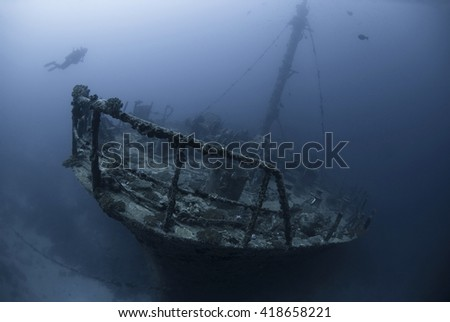 Lonesome scuba diver on a wreck in the dawn in mystical ambiance. - stock photo