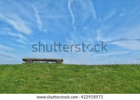 lonesome wooden bench on green grass under the blue sky - stock photo
