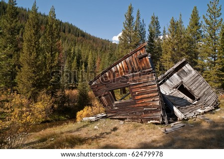 Long-abandoned home or bunkhouse has been left to fall apart through vandalism, weather, time, and cows in the Montana ghost town of Coolidge - stock photo
