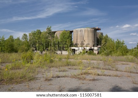 Long ago abandoned concrete industrial site now taken over by trees, brush and weeds. - stock photo