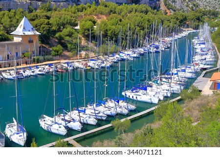 Long and narrow calanque and sail boats tied to the pier, Cassis, France - stock photo