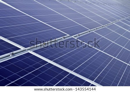 Long array of solar panels in bright sunlight