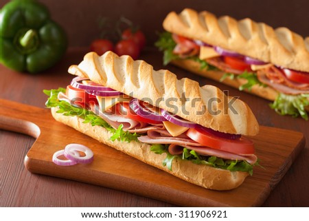 long baguette sandwich with ham cheese tomato lettuce - stock photo