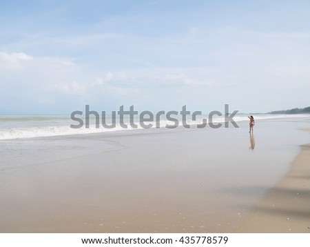 Long beach in Thailand with young woman walk on an empty wild beach as background with blue sky. Woman walking on sandy beach. Waves sweeping away her traces in sand. Beach, travel, concept.  - stock photo