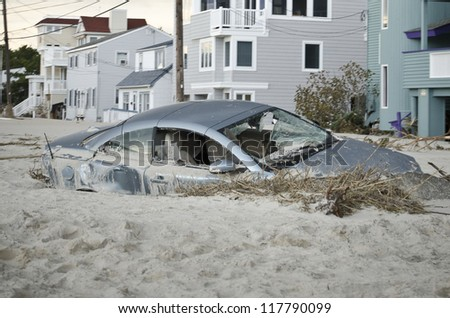 LONG BEACH ISLAND,NJ-NOVEMBER 1: A car is badly damaged by the storm surge and sand caused by  Hurricane Sandy in Holgate.Nov 1 2012, Long Beach Island, NJ - stock photo