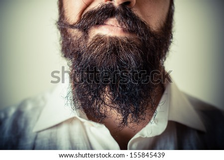 long beard and mustache man with white shirt on gray background - stock photo