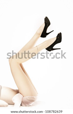 Long beautiful legs in black shoes isolated on white