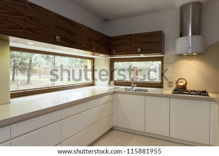 Long beige counter top in modern kitchen interior - stock photo