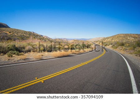 Long bending curve in the road leading into the arid desert wilderness of the American southwest.
