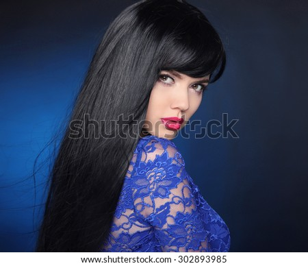 Long Black Hair. Beautiful model girl with healthy straight shiny hair and sensual lips isolated on blue dark background. Beauty Brunette Woman.  - stock photo