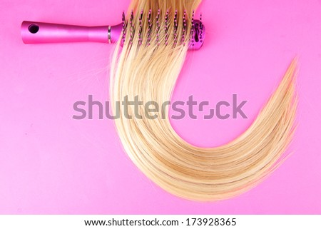Long blond hair with hairbrush on pink background - stock photo