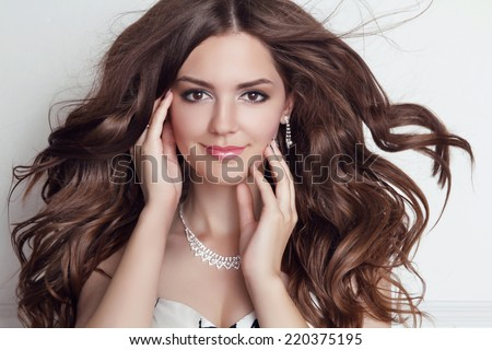 Long blowing hair. Beautiful brunette girl model with makeup, fashion jewelry, wavy hairstyle. - stock photo