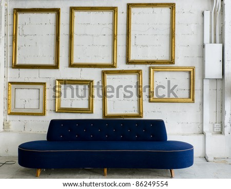 Long blue fabric sofa and gold picture frame on white wall