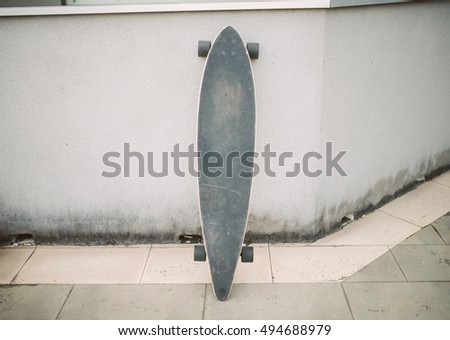 Long board in the street leaning against a wall