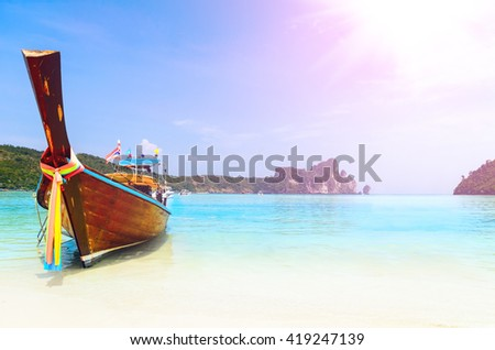long boat at the beach with lens flare at koh Phi-Phi, Thailand - stock photo