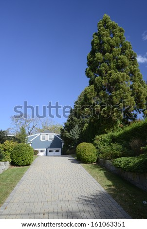 long brick driveway going up hill to a blue house - stock photo