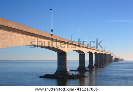 Long bridge across open water with blue sky. - stock photo