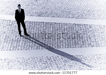 Long businessman shadow in urban background. - stock photo