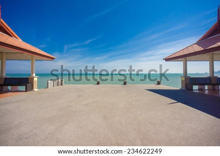 Long concrete pier on tropical beach with two canopy - stock photo