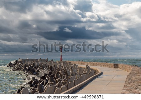 Long concrete pier with line of tetrapod breakwaters and red lighthouse on the edge in the Baltic sea at stormy weather - stock photo