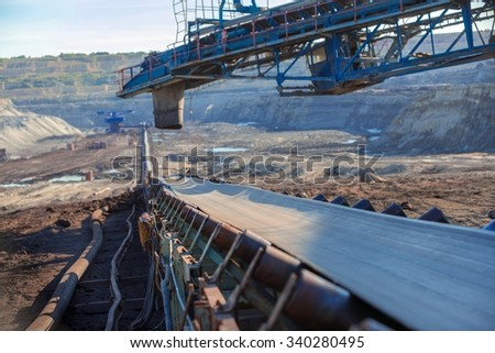 Long conveyor belt transporting ore to the power plant - stock photo