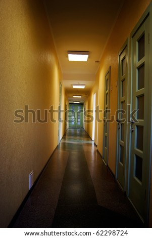 Long corridor in hospital with doors and chairs - stock photo