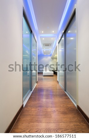 Long corridor in luxury apartment with colorful ceiling lights - stock photo