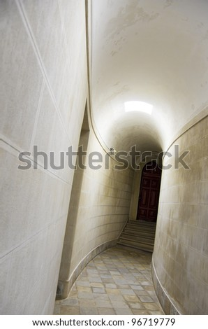 Long corridor with white walls and brown door inside of a building