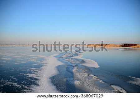 long crack with snow in the frozen lake - stock photo