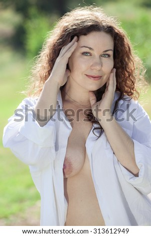 Long curly hair pretty woman touching her face with hands, nude breast, summer season - stock photo