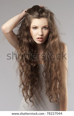 long curly hair young cute girl in a porteait on gray background - stock photo