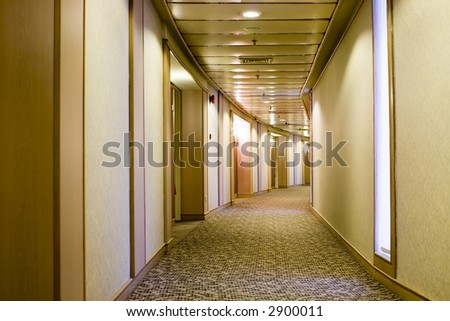 Long curved carpeted hallway in a hotel - stock photo