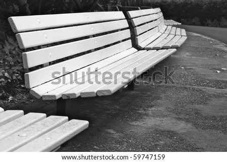 Long curved row of white park benches in B&W - stock photo