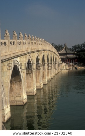 Long curved white stone bridge with many arches over a lake in the Summer Palace, Beijing
