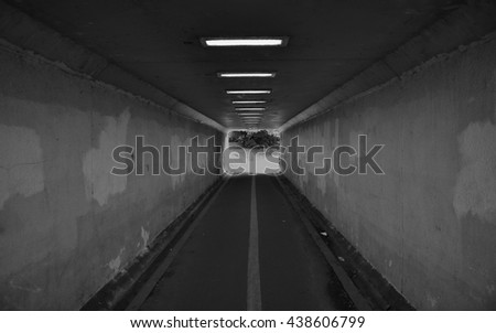 Long Dark Subway Tunnel in Black and White - stock photo