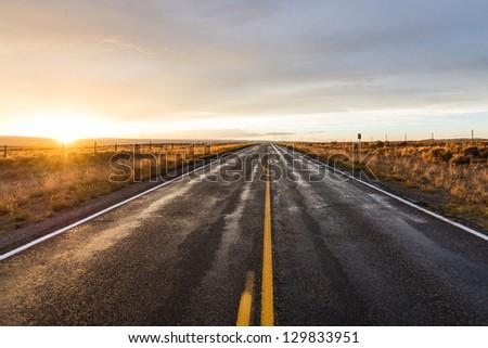 Long desert highway at the sunset - stock photo